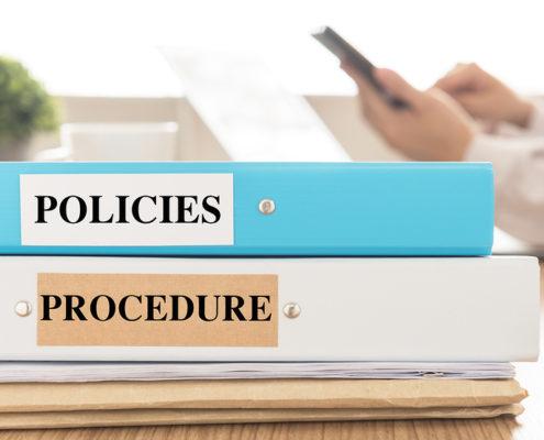 Policies and Procedures doucuments place on desk in meeting room. Policy Procedure concept.